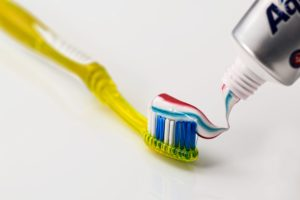 yellow toothbrush with toothpaste on it