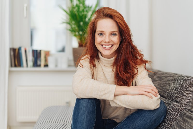 Red-haired woman sitting on couch smiling